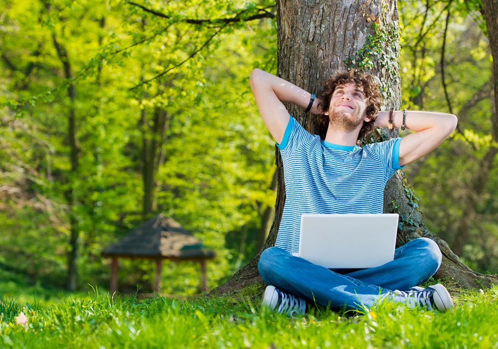Young man in a park enjoying with laptop