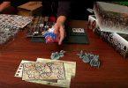 voldor montre des dés au dessus du débalage du jeu de plateau conan