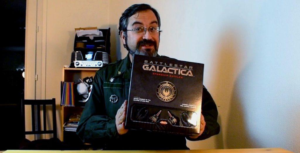 Merlin tient en main la boite de Battlestar Galactica Starship Battles